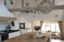 a white kitchen with black and butcherblock countertops,wooden beams, a crystal chandelier and gold fixtures