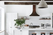 a white kitchen with planked cabinets, a large kitchen island, a white subway tile backsplash, dark wooden beams and a concrete pendant lamp
