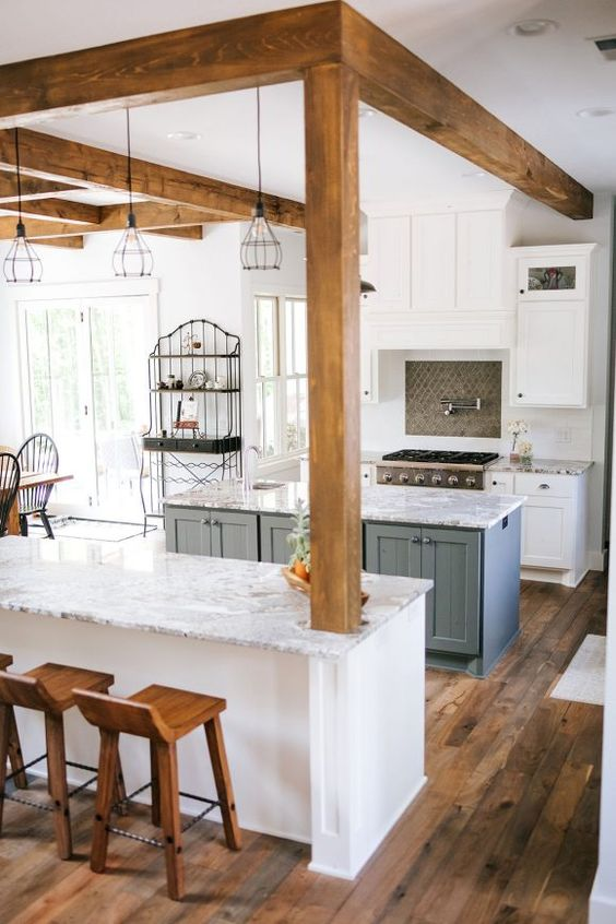 a white kitchen with shaker cabinets, a grey tile backsplash, a slate grey kitchen island, white stone countertops and wooden beams with pendant lamps hanging from them