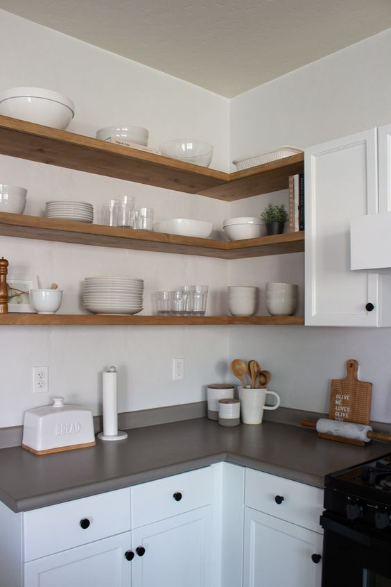 a white kitchen with shaker cabinets, grey countertops and a white backsplash, light-stained corner shelves is a lovely monochromatic space