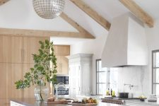 a white light-filled kitchen with sleke cabinets, a large hood, wooden beams, sphere lamps, a large kitchen island with an eating space