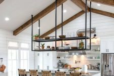 a white modern farmhouse kitchen with planked walls, wooden beams, a large kitchen island, woven chairs and a suspended shelf