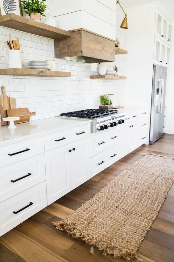 a white modern farmhouse kitchen with shaker cabinets, black fixtures, floating shelves and a hood clad with wood