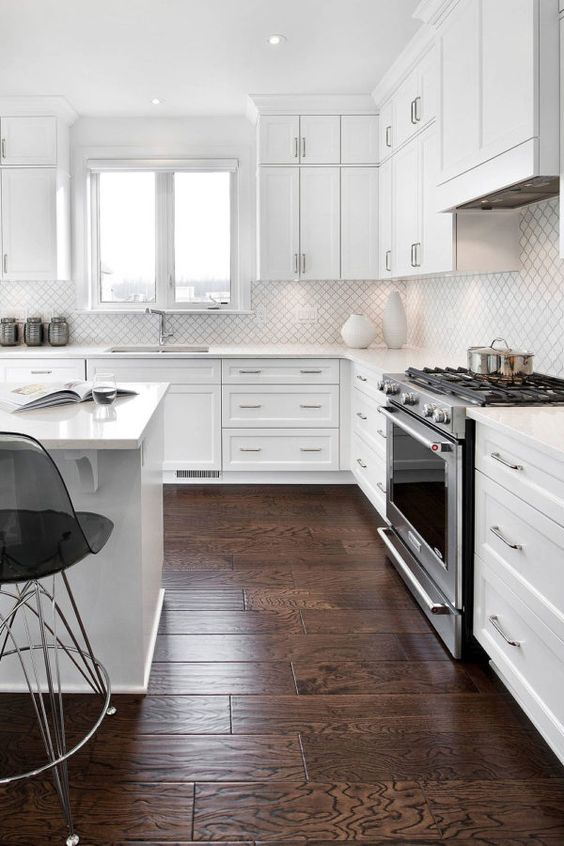 a white modern kitchen with shaker cabinets, a white small scale arabesque tile backsplash, black sheer stools and shiny fixtures