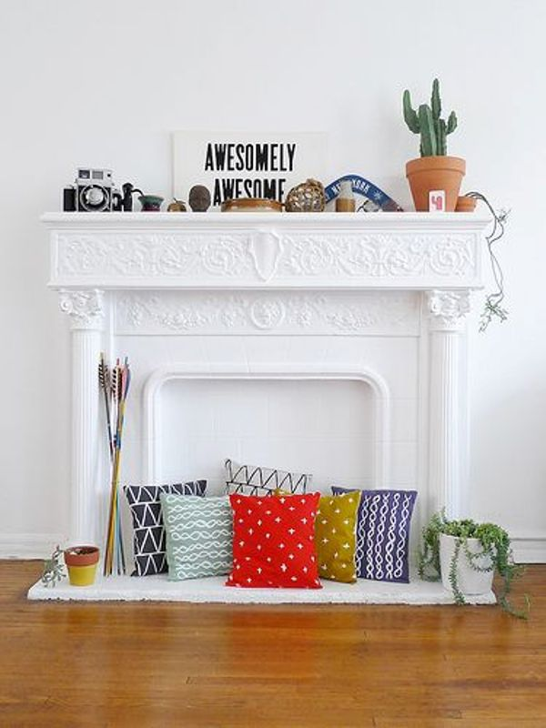 a white non-working fireplace with a refined mantel, with colorful pillows and arrow inside it, with some decor on the mantel