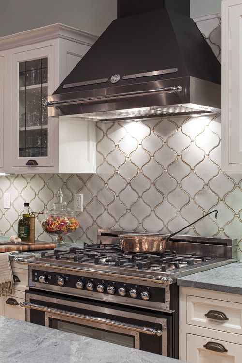 a white retro kitchen with shaker and glass cabinets, a statement black cooker and a hood, a white arabesque tile backsplash and grey stone countertops