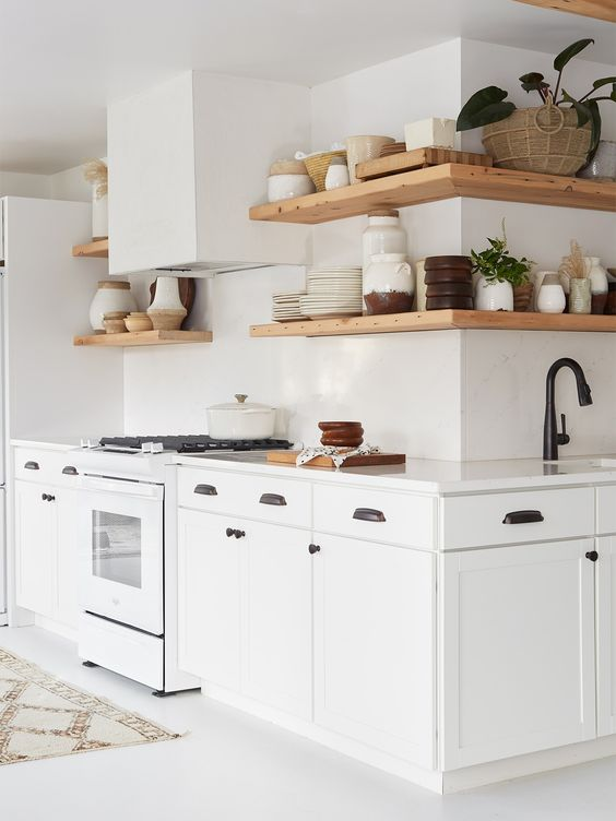 a white shaker style kitchen with white countertops and a backsplash, black fixtures and floating shelves covering the corner too