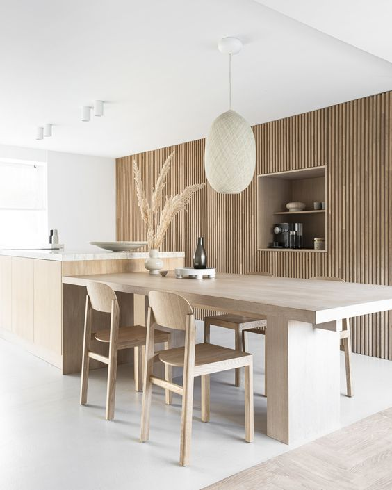 an airy Japandi kitchen with a woode slab wall that hides storage space, a large kitchen island and table here, some lovely chairs