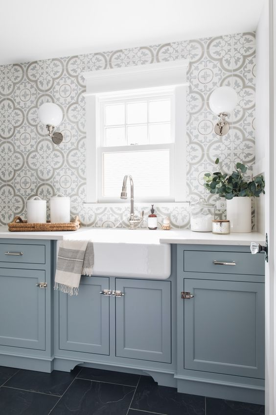 an airy blue kitchen with lovely Moroccan tiles, white stone countertops and neutral fixtures is a very chic and serene space