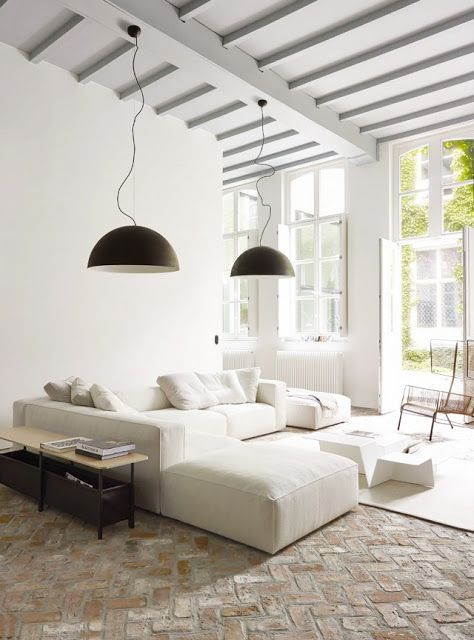 an airy contemporary living room with a white sectional, a console table, a sculptural coffee table and black pendant lamps