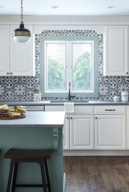 an airy cottage kitchen with white shaker cabinets, blue printed Moroccan tiles, a mint blue kitchen island and a frame