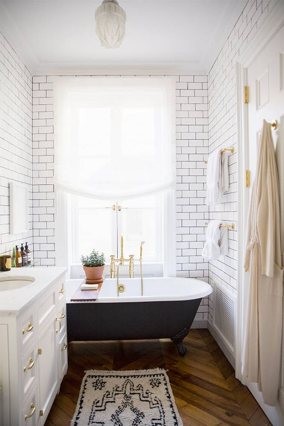 an airy modern bathroom clad with white subway tiles, with a black clawfoot tub, a white vanity with gold touches and gold fixtures
