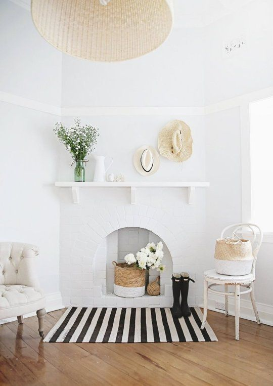 an airy space with chic chairs, a brick fireplace with a basket and white blooms, hats and vases is very cozy and welcoming