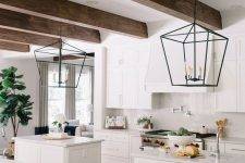 an airy white kitchen with shaker cabinets, a hood, stained wooden beams and two small kitchen islands plus pendant lamps