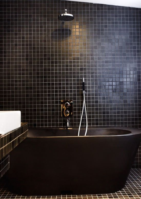 an all-black bathroom clad with square tiles, with a black stone bathtub, a vanity clad with black tiles and a white sink