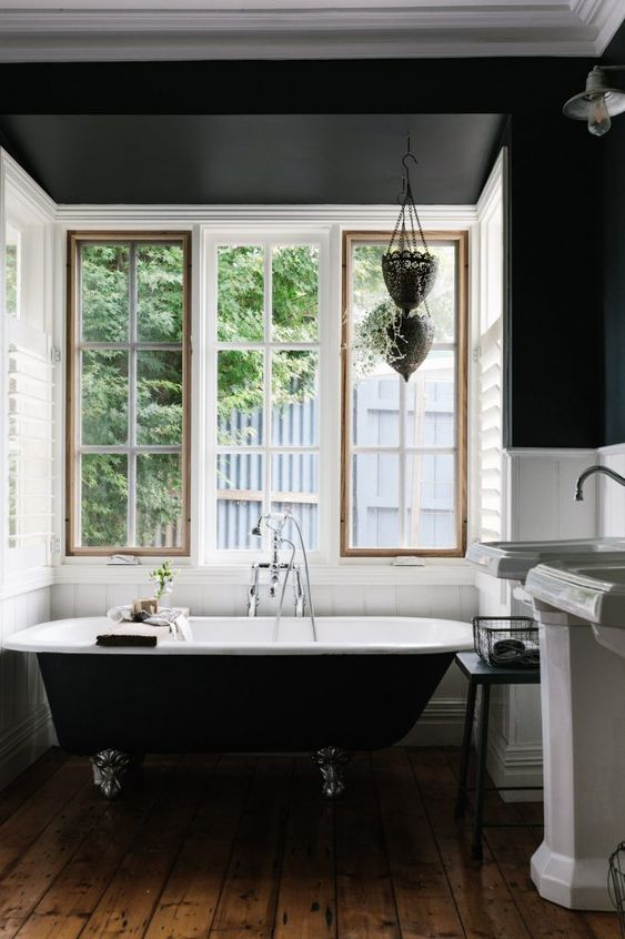an art deco bathroom with black walls and white planks, a black clawfoot bathtub, free-standing sinks and a window