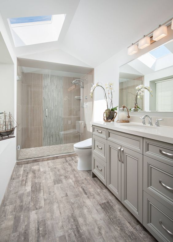 an attic bathroom clad with wood look and stone tiles, a grey vanity, white appliances, a skylight is a chic and cool idea