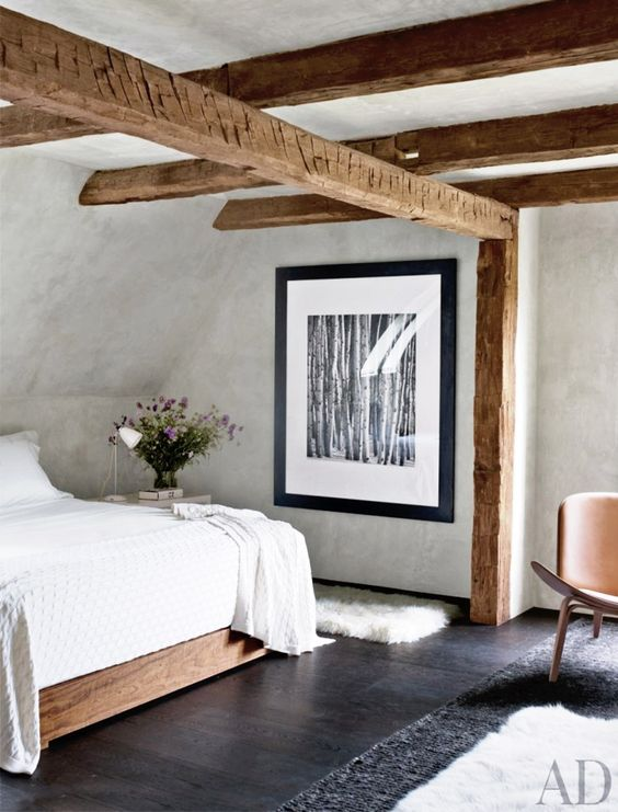 an attic bedroom with a stained bed, stained wooden beams, a leather chair and neutral bedding is a cool idea