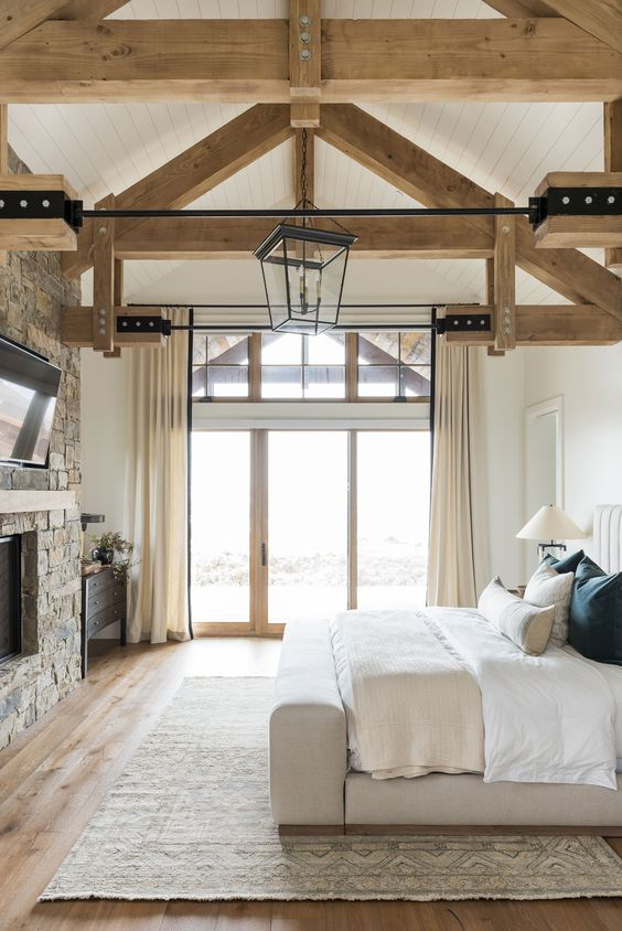 an attic cabin bedroom with wooden beams on the ceiling, a stone clad fireplace, a neutral bed with neutral bedding and a black dresser