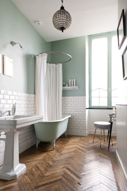 an eclectic bathroom with green walls and white subway tiles, a green clawfoot tub, a pedestal sink, a round stool and a vanity is glam