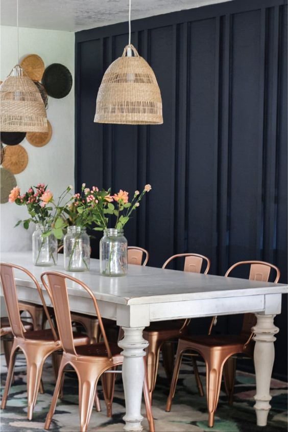 an eclectic dining space with a black paneled wall, a vintage white table, copper chairs, woven lamps and decoative plates