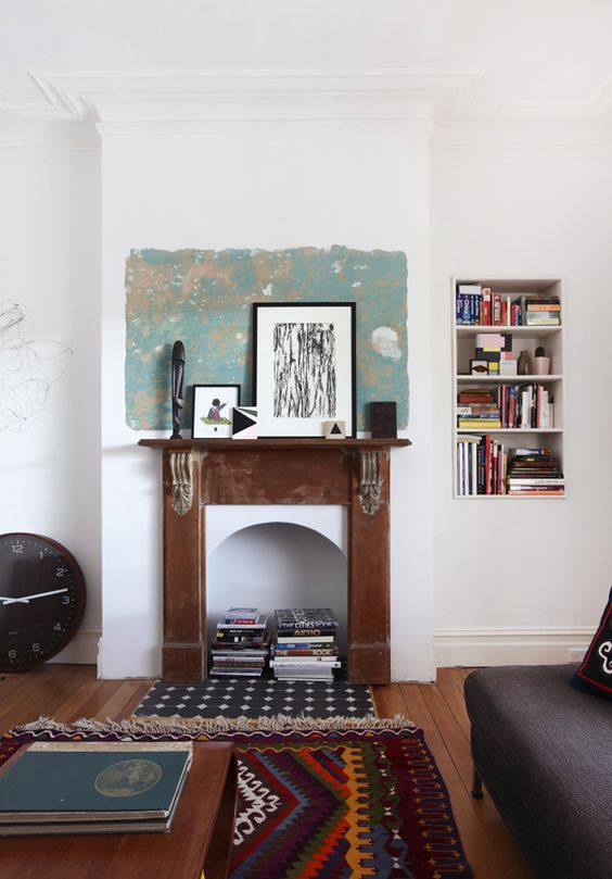an eclectic living room with a grey sofa, a fireplace wiht a shabby chic mantel, some artworks and books inside the fireplace