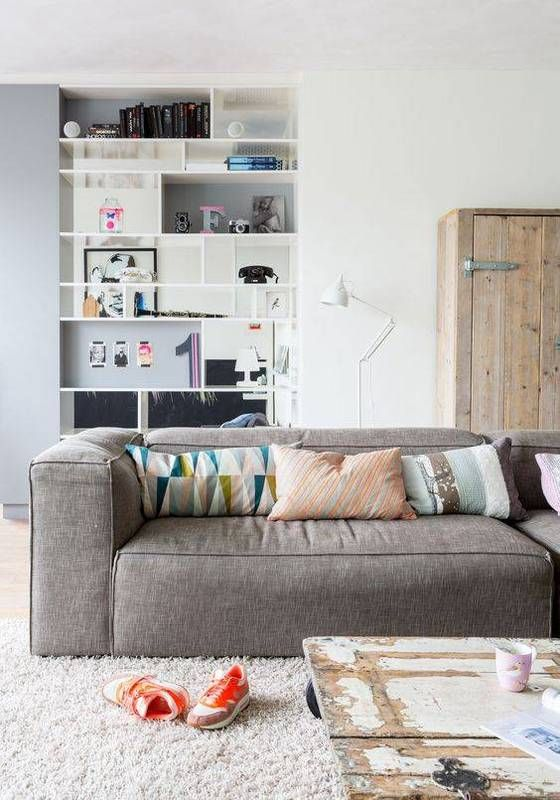 an eclectic living room with a rough wood storage cabinet, a grey low sofa, a shabby chic coffee table and a built-in shelving unit