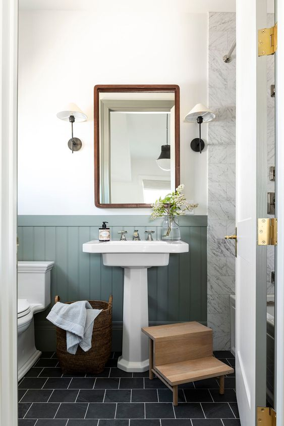 an elegant bathroom with green panelling, a pedestal sink, a wooden ladder, a mirror in a wooden frame and vintage sconces