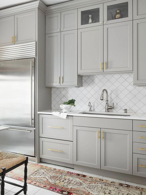 an elegant dove grey kitchen with shaker cabinets, gold handles, a white arabesque tile backsplash and gold and chrome touches