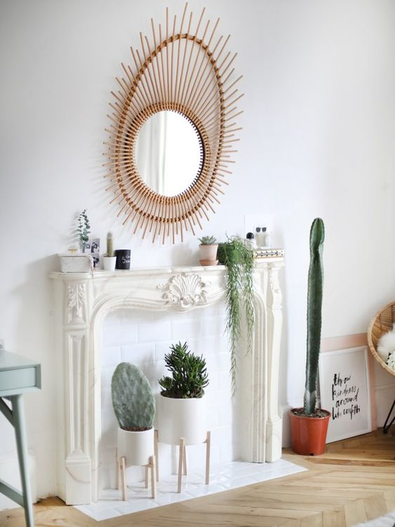 an elegant faux fireplace with potted plants and cacti on display, with a chic and beautiful mirror and some bottles