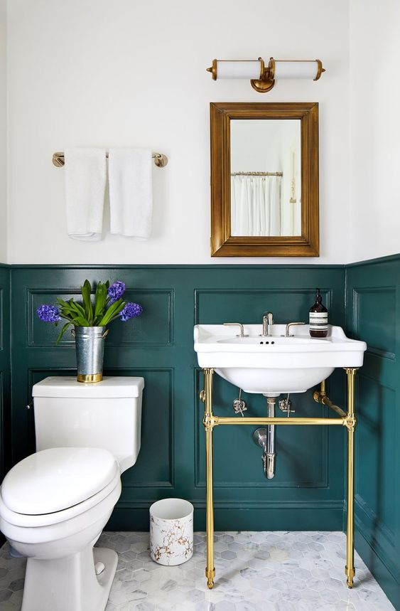 an elegant powder room with teal panels on the walls, a console sink, a mirror in a brass frame, white appliances and neutral towels