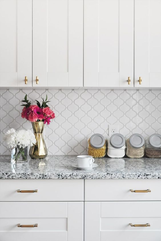 an elegant white kitchen with shaker cabinets and gold fixtures, a small scale arabesque tile backsplash and terrazzo countertops is very cool