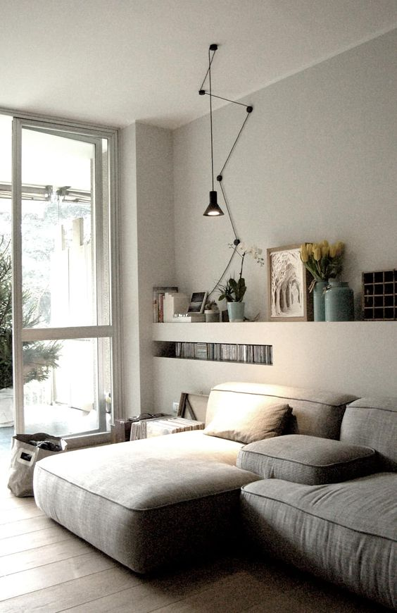an ethereal Scandi living room with a low grey sectional, built-in shelves, a black pendant lamp and some books