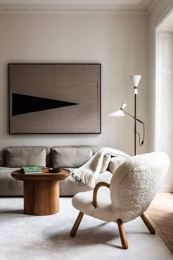 an ethereal Scandinavian living room with a grey low sofa, a creamy chair, a wooden coffee table, a floor lamp and a bold artwork