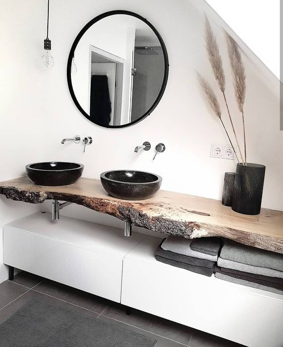 an exquisite bathroom in white, with concrete tiles, a white vanity, a living edge top, black stone vessel sinks and black vases