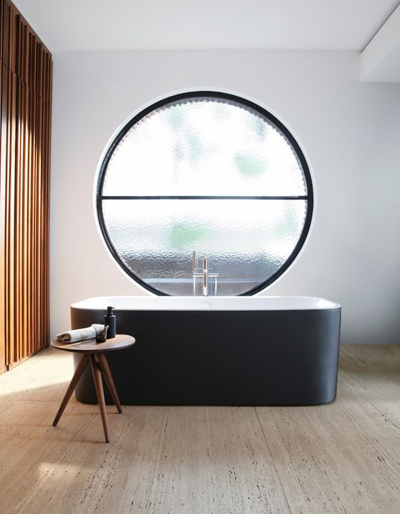 an exquisite contemporary bathroom with a wooden slab accent wall, a wooden floor, a sleek black bathtub and a large frosted glass round window
