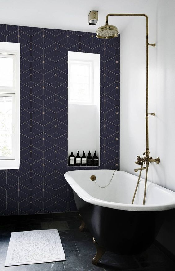 an eye-catchy bathroom with navy and gold geo tiles, a black tile floor, a black clawfoot bathtub and gold fixtures is cool