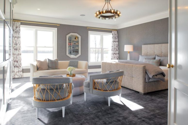 an eye-catchy grey bedroom with an upholstered bed, a creamy sofa, grey chairs, a round table, a chic chandelier and touches of gold