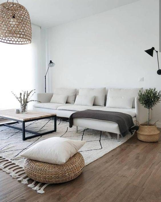 an inviting Japandi living room with a cool neutral sectional, a low coffee table, a jute pouf and a pillow and a woven pendant lamp