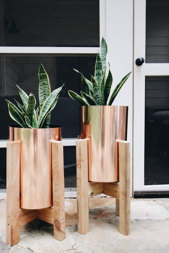 lovely copper planters in wooden stands are a gorgeous and stylish idea for any modern outdoor or indoor space