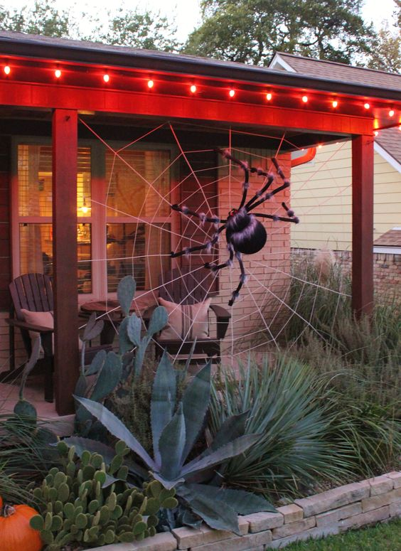 a back porch decorated with a giant spiderweb and a fluffy spider is a cool idea to style your outdoor space for Halloween without much effort