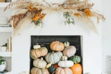 02 a contemporary fall fireplace styled with lots of heirloom pumpkins stacked on each other and with a grass arrangement over it