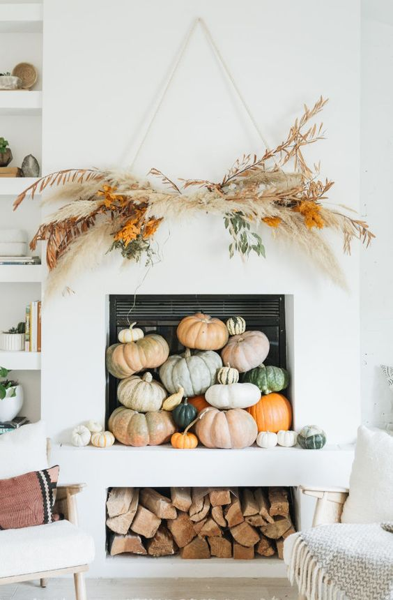 a contemporary fall fireplace styled with lots of heirloom pumpkins stacked on each other and with a grass arrangement over it