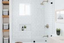 02 a mid-century modern black and white bathroom with subway tiles and a bathtub shower space with a small window placed high
