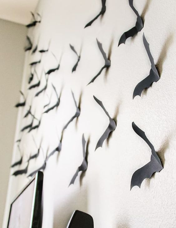 attach black paper bats to the wall to give a Halloween feel to the space at once and make it cool easily