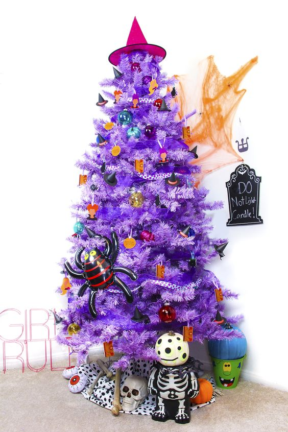 a bright purple Halloween tree with colorful ornaments and pumpkins, a witch hat and a spider is all fun