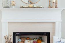 a cute fall fireplace decor with pumpkins