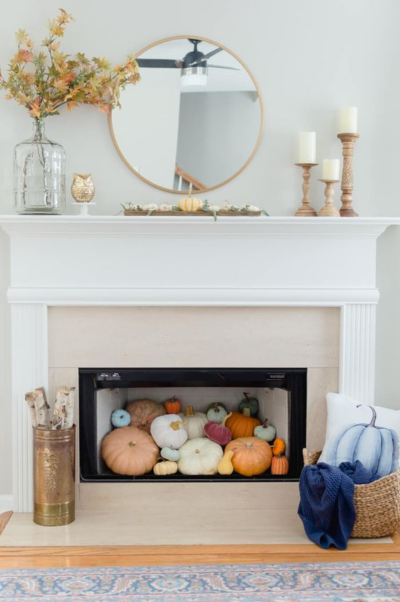 a contemporary fireplace with colorful pumpkins inside, firewood and a blue pumpkin pillow plus some leaves on the mantel