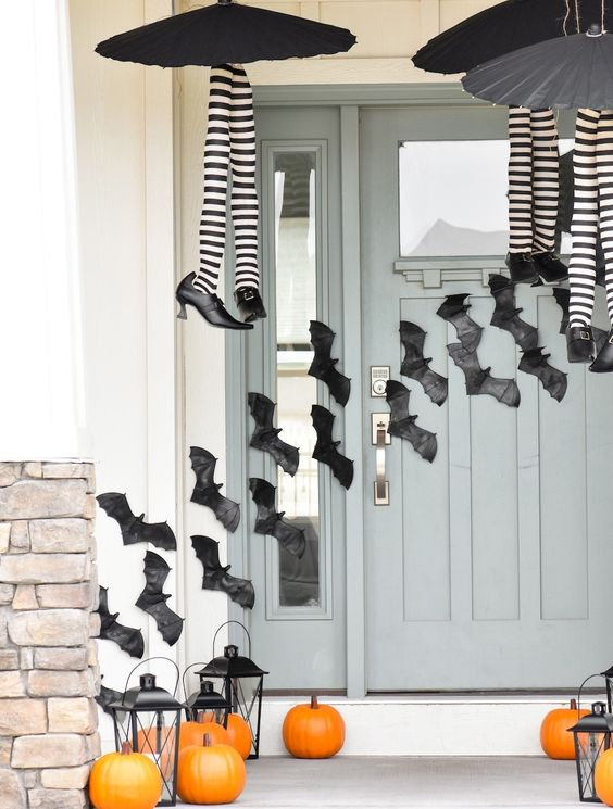 black paper bats attached to the wall and door, witches' legs and black candle lanterns and orange pumpkins make the porch Halloween-like
