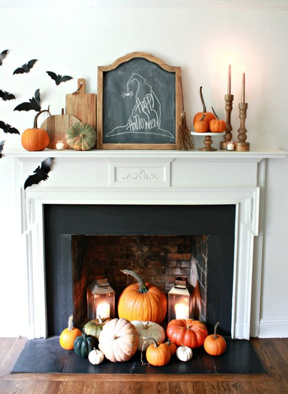 a fireplace with colorful pumpkins and candle lanterns easily turned into a Halloween one with black paper bats attached